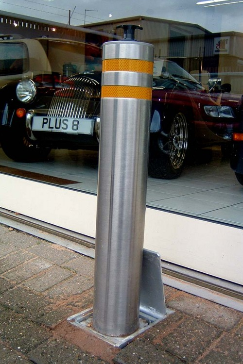 Retractable security bollards in use to protect a car show room and control parking for client car park.